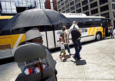 Tommy Fowler (Left) shields himself from the sun as he waits to board a bus during a prolonged heat wave in Dallas, Texas