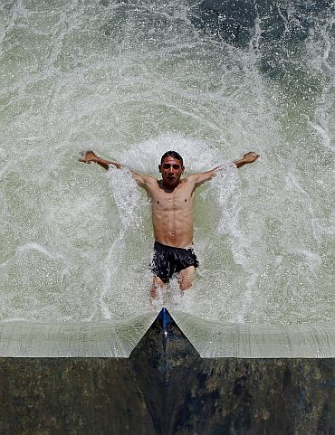A man cools off in Dambovita river in central Bucharest as temperatures reached 36 degree Celsius (96.8 degree Fahrenheit) in southern Romania