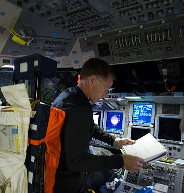STS-135 Commander Chris Ferguson is pictured at the commander's station on the flight deck of space shuttle Atlantis during the mission's initial day of activities in Earth orbit
