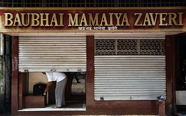 An owner closes his jewellery shop at Zaveri Bazaar