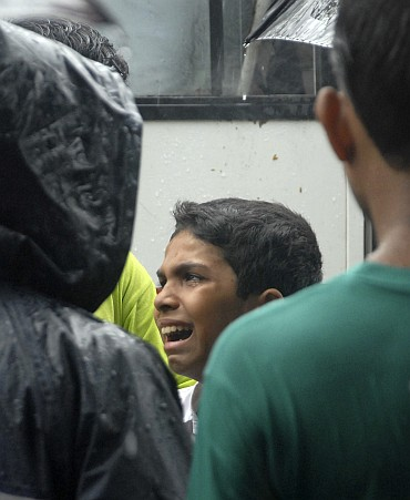A blast victim's brother cries at a funeral in Mumbai