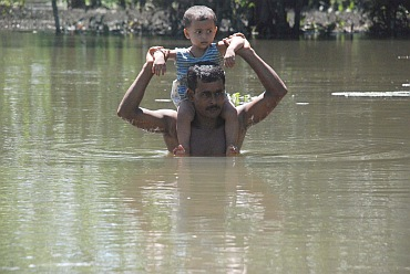 A father wades through water with his son in Lakhimpur