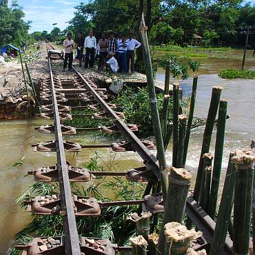 Officials check railway tracks that were damaged because of the floods in Lakhimpur