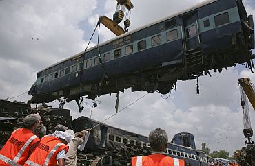 Rescue workers help to move a carriage, lifted by crane, from Kalka mail which derailed near Fatehpur on July 10, killing 69.