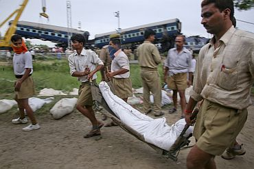 Rescue workers carry the body of a victim after Kalka mail derailed near Fatehpur.