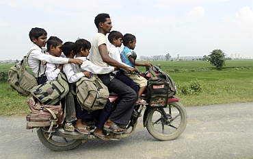 A man rides a motorcycle carrying six children on their way back home from school at Greater Noida