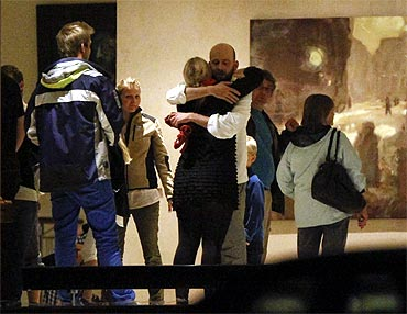 People embrace inside a hotel where relatives of victims and survivors of the shooting gathered