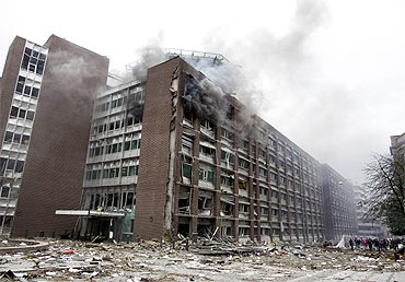 Smoke billows from a building at the site of a powerful explosion that rocked central Oslo