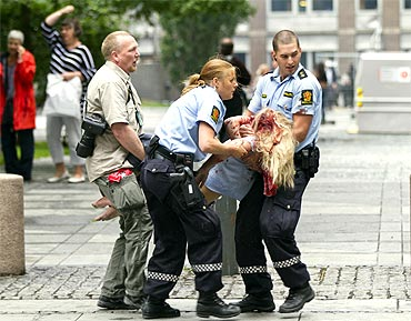 Policemen evacuate an injured woman after a powerful explosion rocked central Oslo