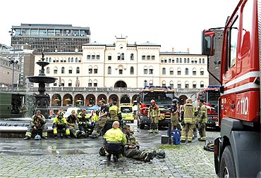 Rescue workers gather near the site of a powerful explosion that rocked central Oslo