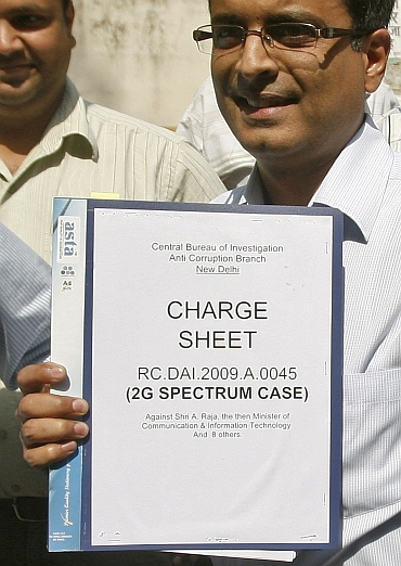 CBI officials carry the 2G spectrum case charge sheet to a court in New Delhi