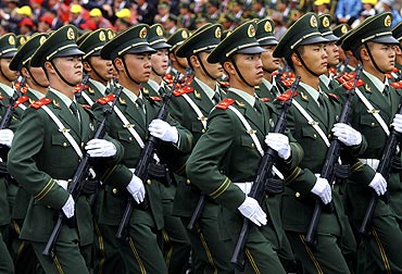 Paramilitary policemen march in formation in front of the Potala Palace during a parade celebrating the 60th anniversary of Tibet's peaceful liberation