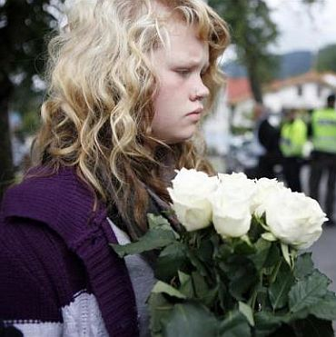 A girl lays flowers in front of a hotel where relatives and survivors of a shooting rampage on nearby Utoeya island gather after a memorial service in Sundvollen
