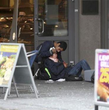 A passer-by comforts an injured woman
