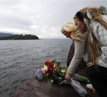 People place flowers in front of Utoeya island, northwest of Oslo