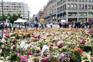 Candles and flowers are placed in tribute to the victims of the twin terror strike in Oslo