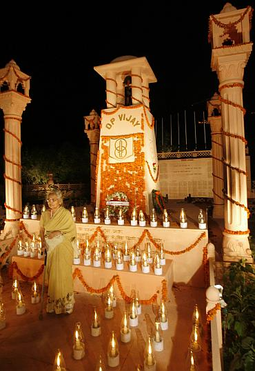 A woman walks near the illuminated war memorial during Vijay Diwas in Drass