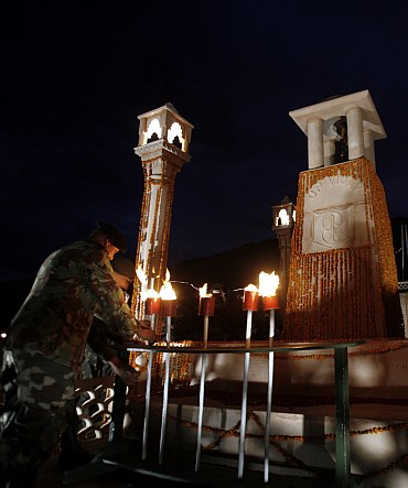A senior Army officer places a torch at a war memorial during Vijay Diwas celebration in Drass