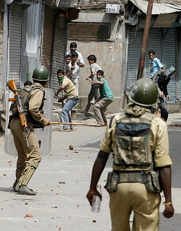 Kashmiri protesters throw stones towards policemen during a protest rally in Srinagar
