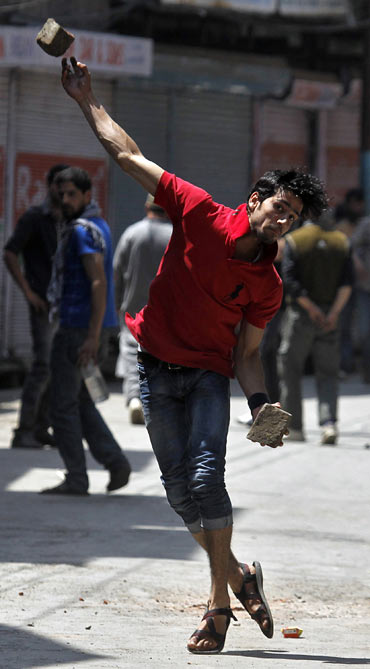A Kashmiri youth throws a piece of brick towards the police during a clash in Srinagar