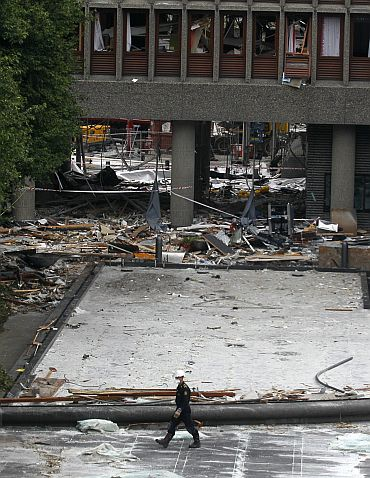 A Norwegian policeman inspects the blast site in front of the destroyed government building in Oslo
