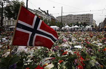 Norwegian flag is placed in a sea of flowers and candles which are placed in memory of those killed in bomb and shooting attack in front of Oslo Cathedral