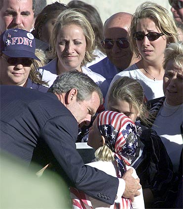 A file photo of George W Bush talking to a young family member of one of the victims of 9/11 strikes