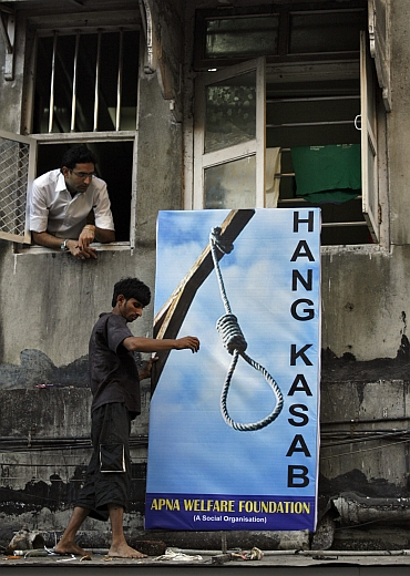 A resident places a billboard about Kasab outside a residential building near the Leopold Cafe, one of the sites of the Mumbai attacks