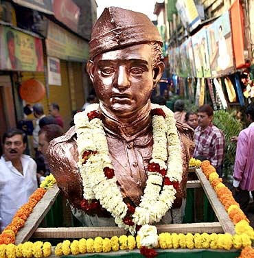 People stand beside a statue of former leader Subhas Chandra Bose to commemorate his birthday in Kolkata