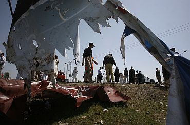 Policemen are seen through a torn billboard as they survey the site of a suicide bomb attack in Swabi on March 30, 2011, that killed 12 persons