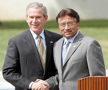 Former Pakistani President Pervez Musharraf shakes hands with visiting former US President George W Bush in Islamabad