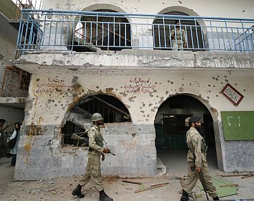 Paramilitary troops walk near a bullet-ridden wall at the Jamia Hafsa, the female Islamic seminary of the Lal Masjid in Islamabad.