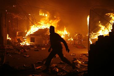 A man runs past a blaze after a suicide explosion at a market in Lahore