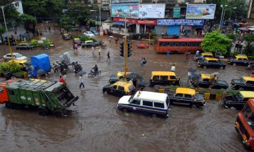 Vehicles make their way through a flooded street in Mumbai Central