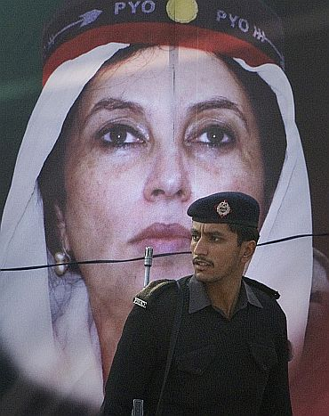 A policeman walks past an image of Benazir Bhutto on her death anniversary