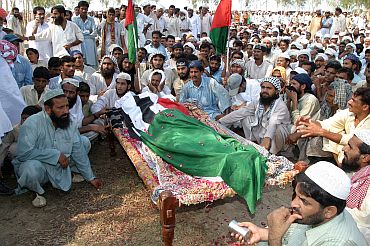 Villagers sit next to the body of Pakistani militant from the outlawed Lashkar-e-Jhangvi near Multan