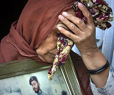 Irshad Bibi, 69, grieves while posing for the media with a picture of her son, former n