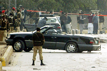 Pakistani soldiers stand guard near former president Musharraf's motorcade car at the site of a suicide blast in Rawalpindi in December, 2003.