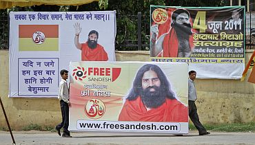 Supporters of Baba Ramdev carry his portrait before raising it in the Ramlila grounds, the venue of his indefinite fast, in New Delhi