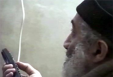 Osama bin Laden is shown holding a remote while watching himself on television in this video frame grab released by the Pentagon