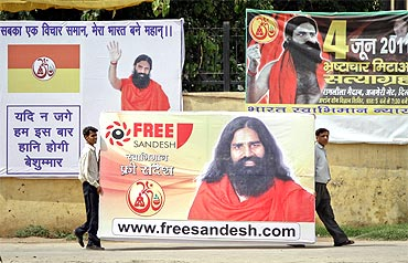 Supporters of Baba Ramdev carry his posters