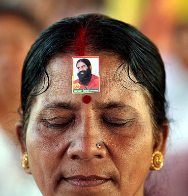A supporter wears an image of Swami Ramdev while listening to his address at the Ramlila Grounds