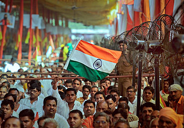 A man waves the national flag during an address by Swami Ramdev