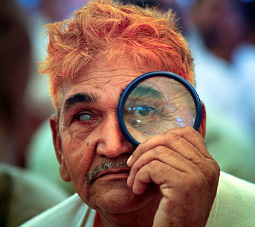 A supporter of Swami Ramdev uses a magnifying glass to watch his address