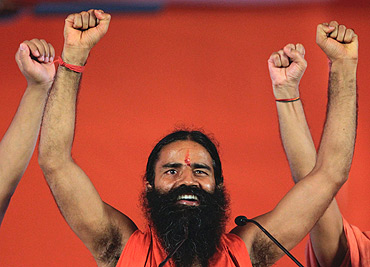 Swami Ramdev raises his hands with supporters at the Ramlila Grounds