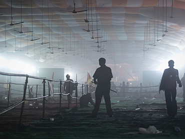 A policeman stands under an empty smoke-filled marquee after Ramdev supporters were dispersed by teargas