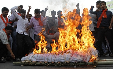 BJP supporters shout slogans in favour of Ramdev as they burn an effigy of PM Singh