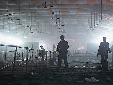 A policeman stands under an empty smoke-filled marquee after supporters of yoga guru Swami Ramdev were dispersed by teargas from the Ramlila grounds in New Delhi late on Sunday