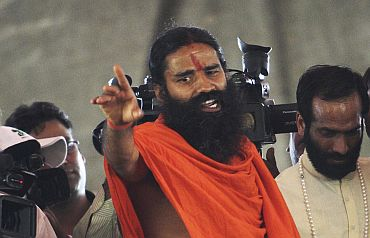 Yoga guru Swami Ramdev speaks during a news conference in New Delhi before his fast