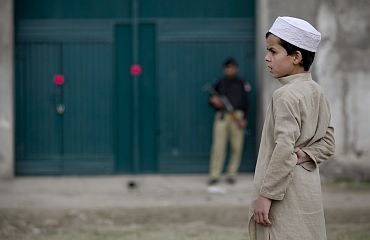 A boy stands in front of the front gates of a compound in Abbottabad, Pakistan where Al Qaeda chief Osama bin Laden was staying before he was killed by US forces